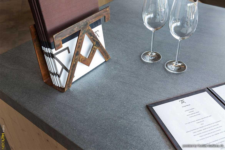 Graue Küchenarbeitsplatte mit Speisekarte und Weingläsern