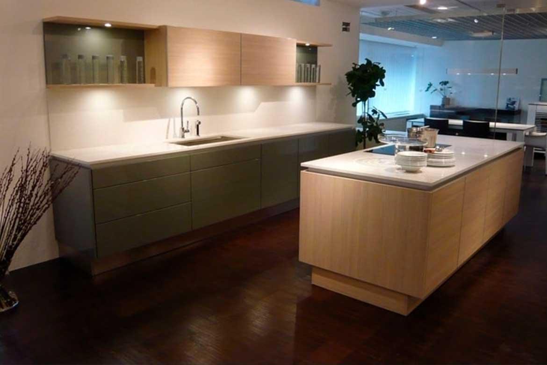 Küche mit weißer Oberfläche und hellbraunen Schränken