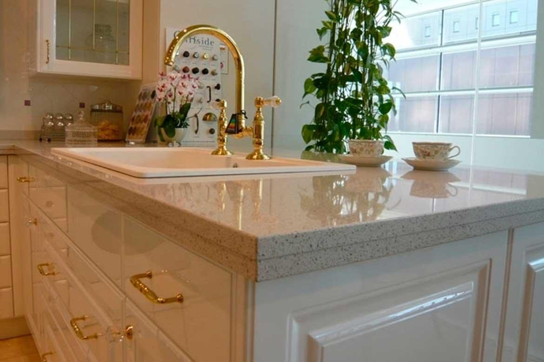 Helle Küche mit goldenem Wasserhahn und goldenen Griffen