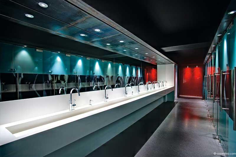 Öffentliches Badezimmer mit hochwertigen Dektonplatten in weiß und Lichtreflexen