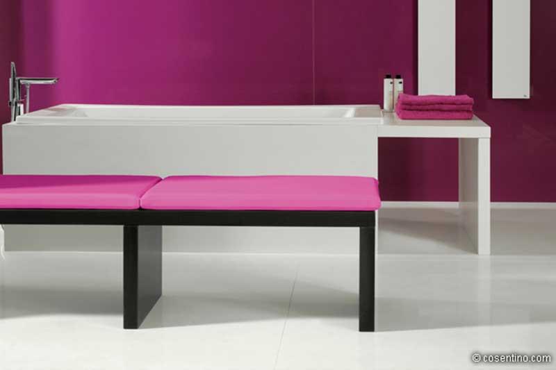 Weiße Badewanne auf Dekton mit pinker Badezimmer Wand