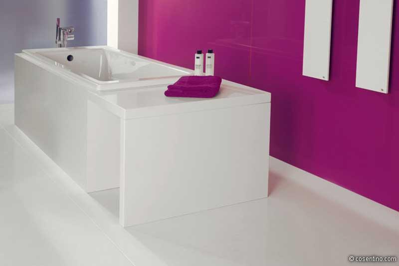 Weiße Badewanne aus hochwertigen Dektonplatten mit einer Pinken Wand
