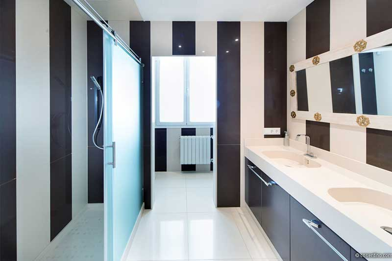 Badezimmer aus hellen Dekton Fliesen und einer Schwarz weiß längs gestreiften Wand